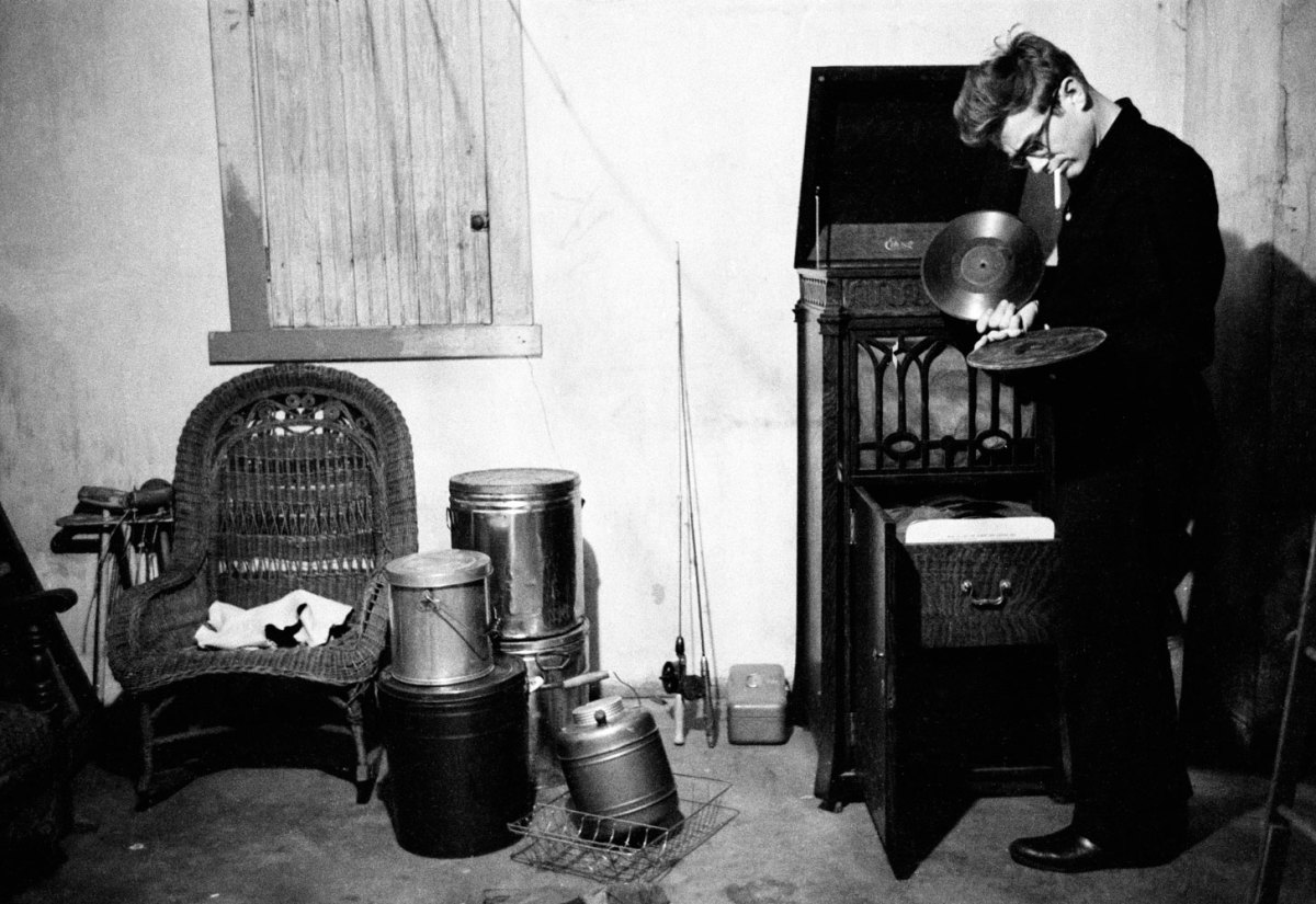 [Photo by Dennis Stock of James Dean looking at records in his aunt and uncle's basement in Indiana, 1955.]