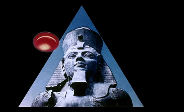 [A glowing, orange UFO soaring past shoulder of the colossal ancient statue of Ramses II in Luxor Egypt from Kenneth Anger's Lucifer Rising]