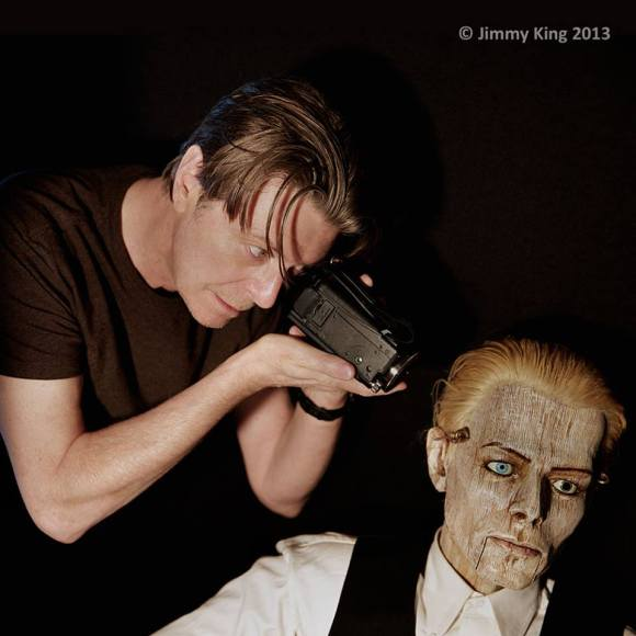 "[Bowie with a puppet produced by Jim Henson's Creature Shop, in the video for 2013 single, ""Love Is Lost."" Assisted by photographer Jimmy King and long-time personal assistant Corinne ""Coco"" Schwab, Bowie wrote, shot, and edited the music video himself for a cost of US$12.99, the cost of the flash drive he had to buy to save the video on his camera.]"